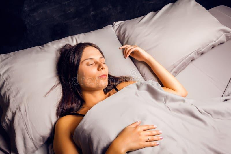 Vrouwenslaap in bed op een donkere achtergrond stock foto's
