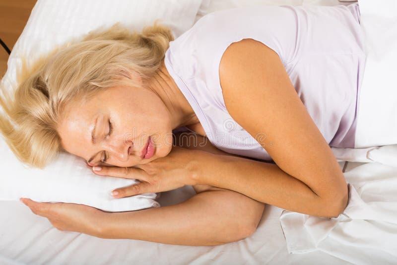 Vrouwenslaap op middelbare leeftijd in bed royalty-vrije stock foto