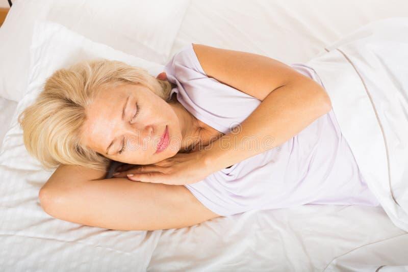 Vrouwenslaap op middelbare leeftijd in bed royalty-vrije stock afbeeldingen