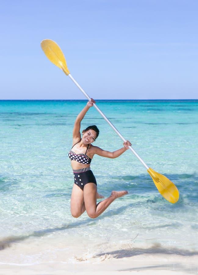 Vrouwensprongen met een peddel op een overzees strand stock foto's