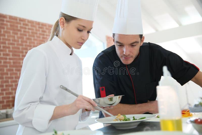 Vrouwenstagiair in het koken van klasse met chef-kok stock afbeelding