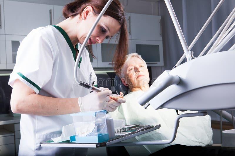 Vrouwentandarts op het werk met een oudere patiënt in tandkliniek royalty-vrije stock afbeelding