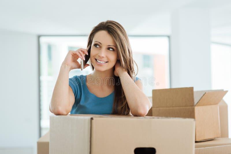 Vrouwentelefoon die binnen haar nieuw huis roepen royalty-vrije stock foto's