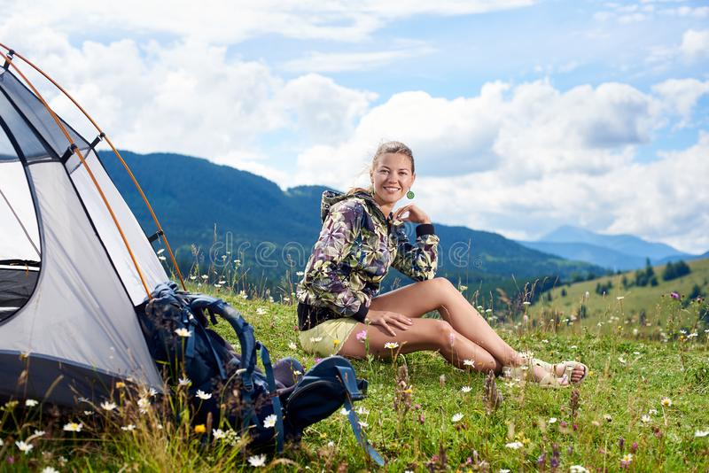 Vrouwentoerist die in bergsleep wandelen, die de zomer van zonnige ochtend in bergen genieten dichtbij tent stock afbeelding