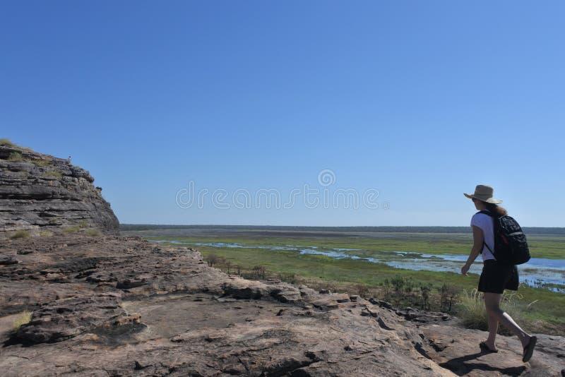 Vrouwentoerist die bij Ubirr-de plaats van de rotskunst op Nationaal het Park Noordelijk Grondgebied van Kakadu wandelen van Aust stock afbeelding