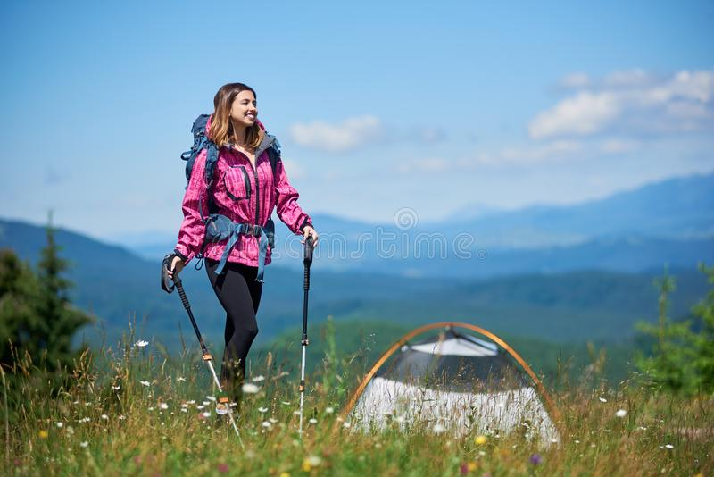 Vrouwentoerist die dichtbij in de bergen met rugzak en trekkingsstokken in de ochtend kamperen stock fotografie