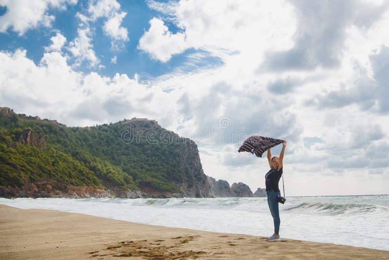 Vrouwentoerist die haar sweater op wind houden bij stormachtige overzees Concept winderig weer op toevluchtgebieden royalty-vrije stock fotografie