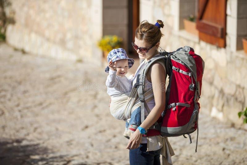 Vrouwentoerist die haar vervoeren weinig zoon in slinger stock afbeeldingen