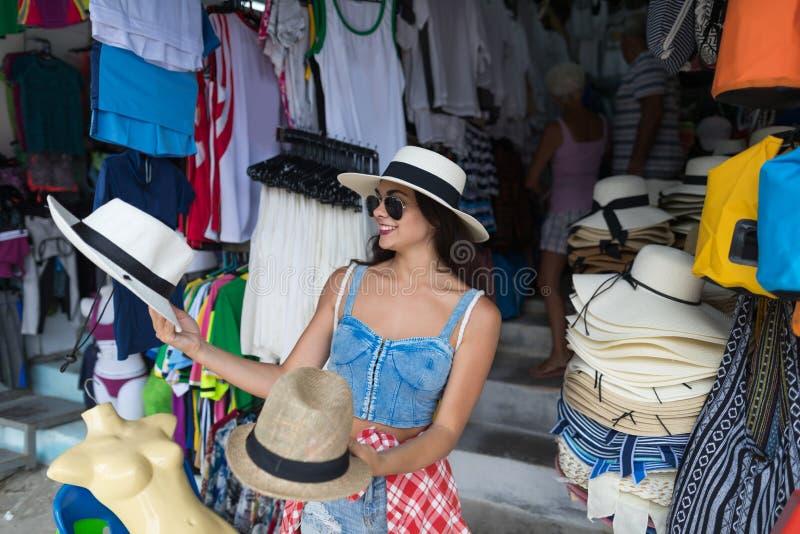 Vrouwentoerist die Hoed op Aziatische Straatmarkt kiezen van Kleren Jong Wijfje die op Vakantie winkelen stock fotografie