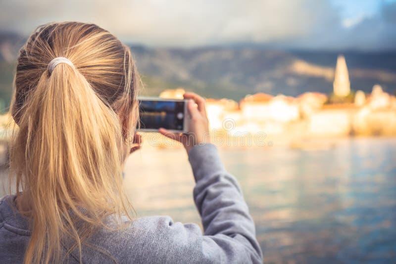 Vrouwentoerist die mobiele foto van mooi landschap met oude stad nemen bij kust op mobiele telefoon tijdens reis royalty-vrije stock foto's
