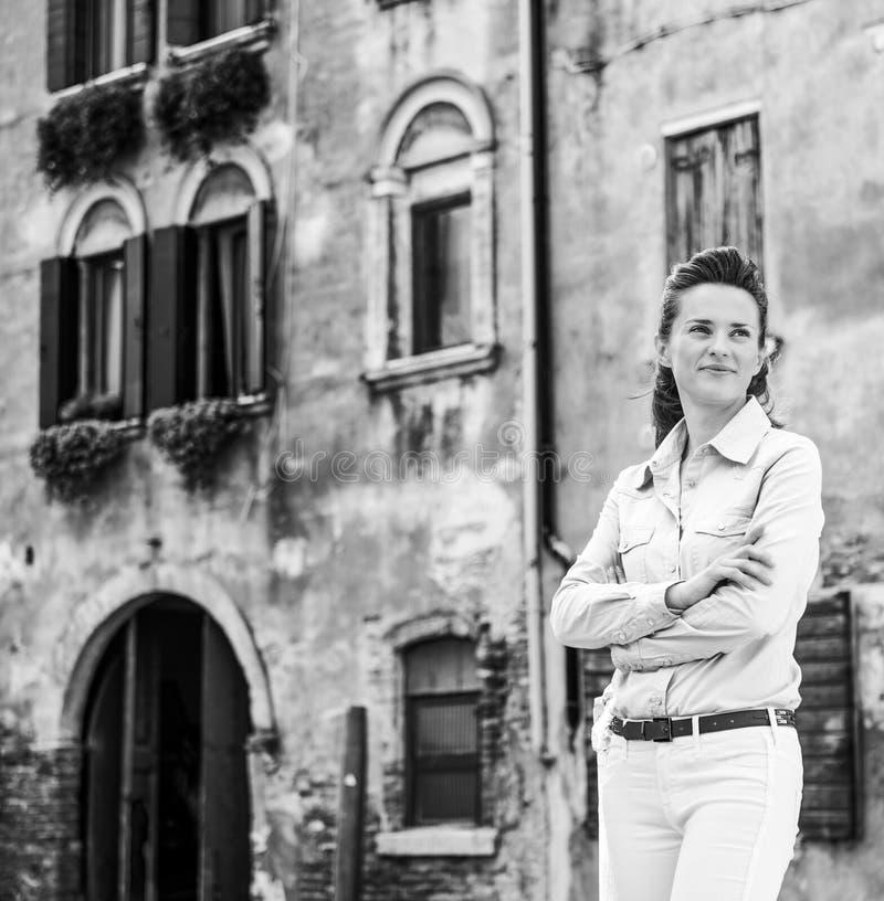 Vrouwentoerist die zich met die wapens bevinden dichtbij het kanaal van Venetië worden gekruist royalty-vrije stock foto