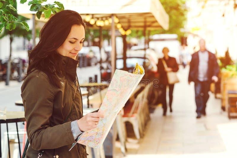 Vrouwentoerist het lopen De aantrekkelijke jonge vrouwelijke toerist onderzoekt nieuwe stad De vrouw met kaart in handen is op zo stock afbeeldingen
