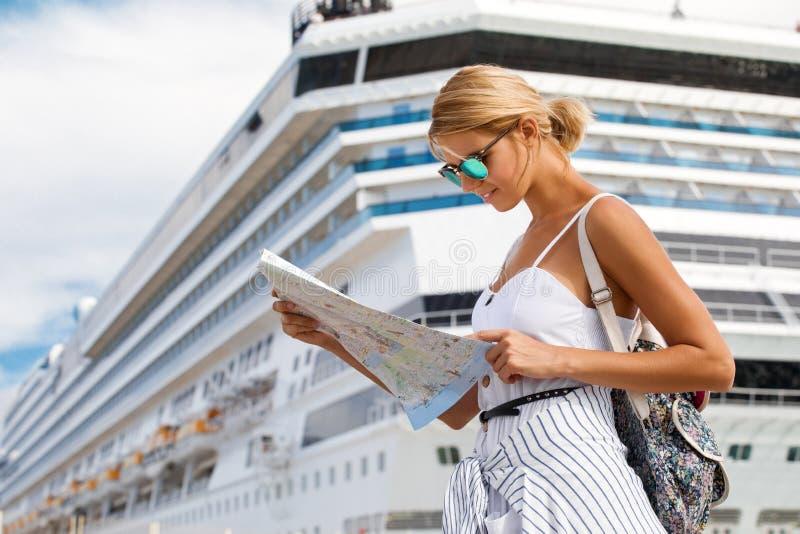 Vrouwentoerist met kaart, die zich voor grote cruisevoering bevinden, reiswijfje stock afbeeldingen