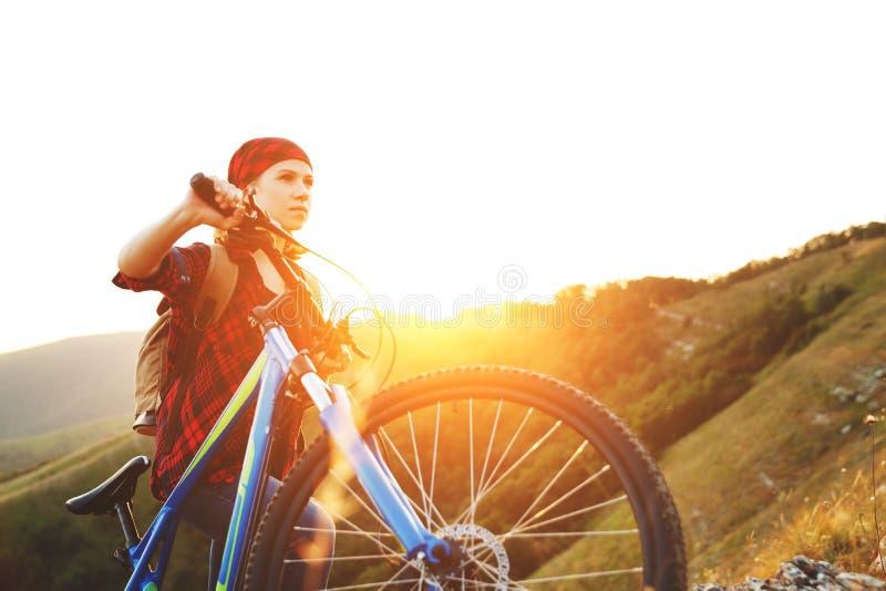 Vrouwentoerist op een fiets boven berg bij zonsondergang in openlucht stock fotografie