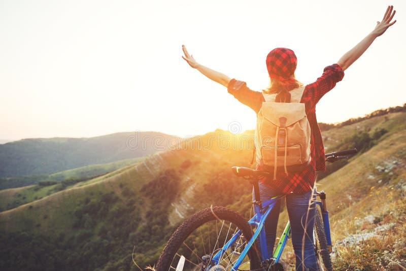 Vrouwentoerist op een fiets boven berg bij zonsondergang in openlucht royalty-vrije stock foto