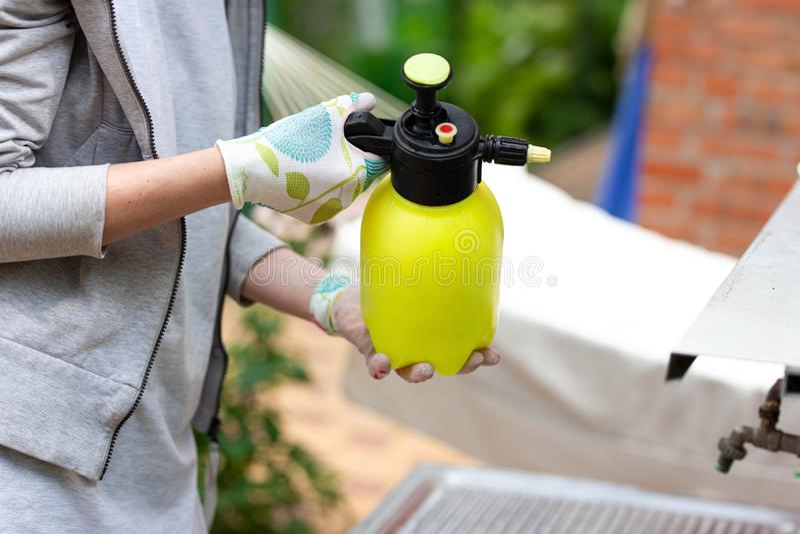 Vrouwentuinman die een spuitbus met pesticide houden stock foto's