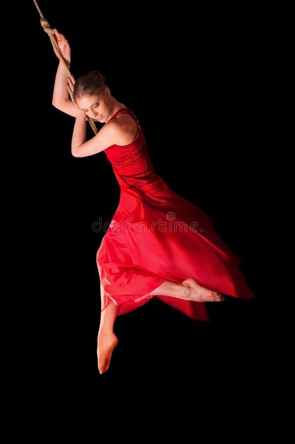 Vrouwenturner in rode kleding op kabel royalty-vrije stock afbeeldingen