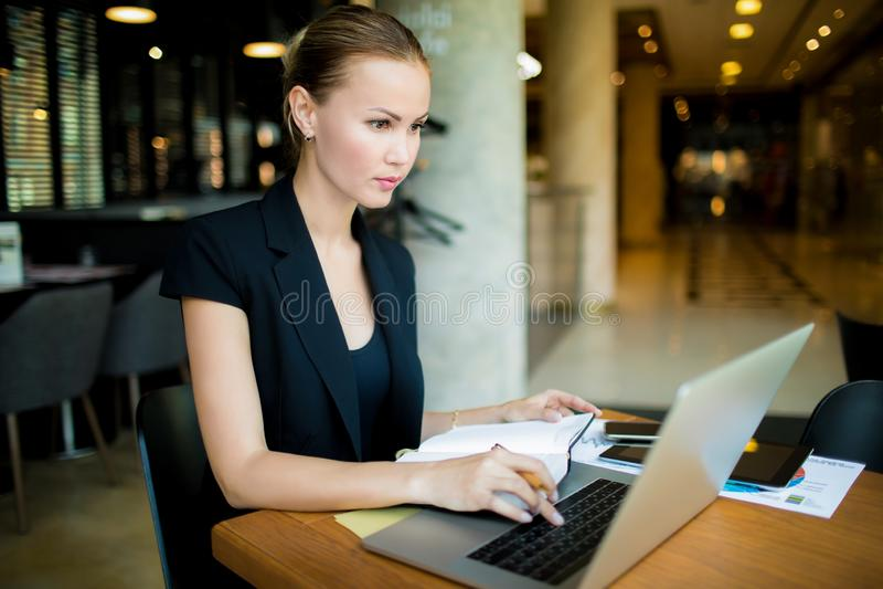 Vrouwenverkoper die informatie bij voorraad de opleiding via laptop computer zoeken stock foto's