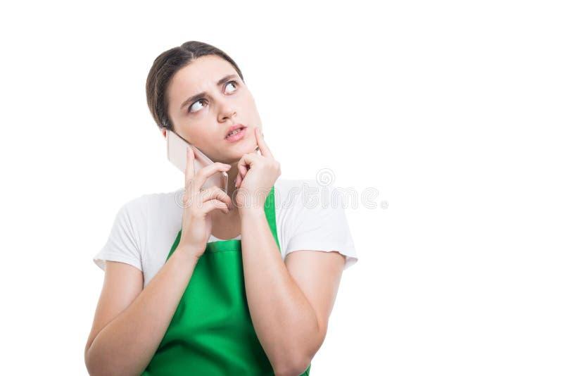 Vrouwenverkoper die met schort bij iets denken royalty-vrije stock afbeelding