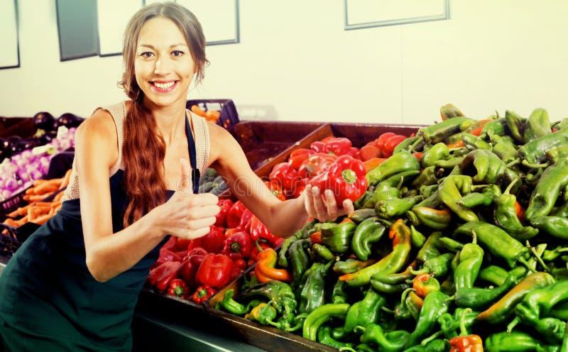 Vrouwenverkoper die schort dragen die rode en groene paprika houden stock foto