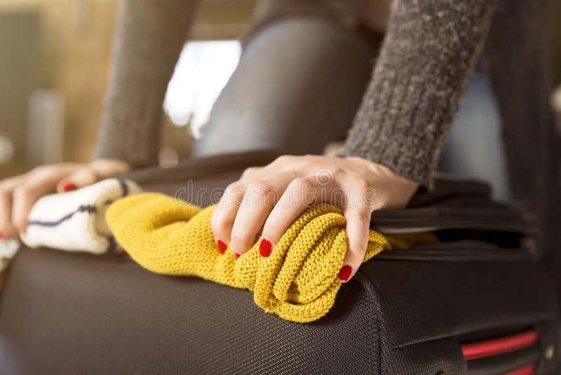 Vrouwenverpakking voor vakantiereis die volledige koffer proberen te sluiten stock fotografie