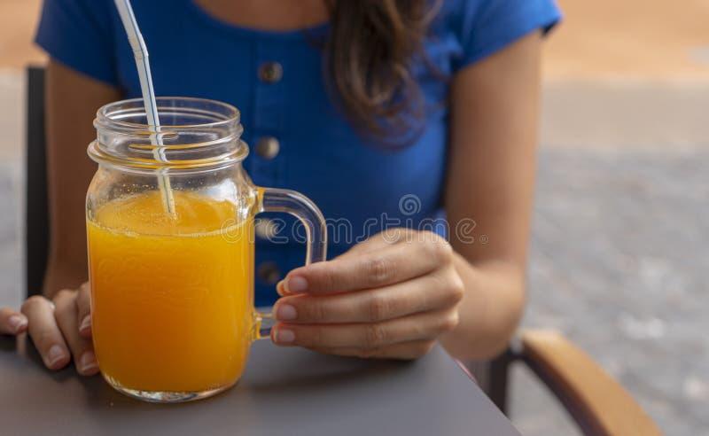 Vrouwenverzadiging, het drinken van een verfrissend sinaasappelsap in een terras Vertrouwen Dame houdt een vloeibaar fruitig glad royalty-vrije stock fotografie