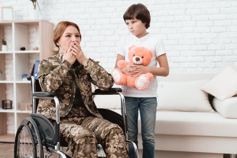 Vrouwenveteraan in rolstoel teruggekeerd huis De zoon is gelukkig om zijn moeder te zien na het terugkeren van het leger stock foto's
