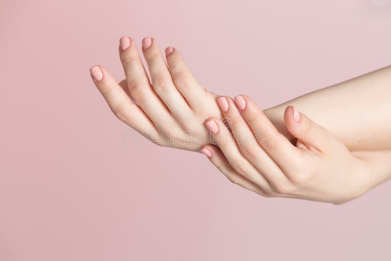Vrouwenvingers met mooie spijkers met roze poetsmiddelmanicure over roze achtergrondclose-upmening stock afbeeldingen