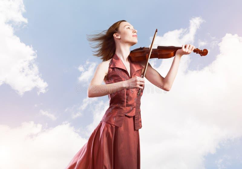 Vrouwenviolist in rode kledings speelmelodie tegen bewolkte hemel stock afbeelding