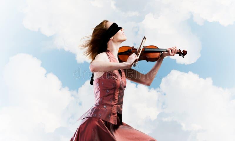 Vrouwenviolist in rode kledings speelmelodie tegen bewolkte hemel royalty-vrije stock afbeelding