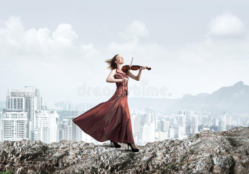 Vrouwenviolist in rode kledings speelmelodie tegen bewolkte hemel stock afbeeldingen