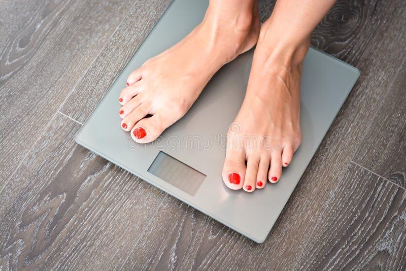 Vrouwenvoeten die op gewichtsschaal stappen die problemen met haar dieet hebben stock foto