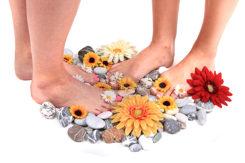 Vrouwenvoeten en bloemen (pedicure tbackground) stock afbeeldingen