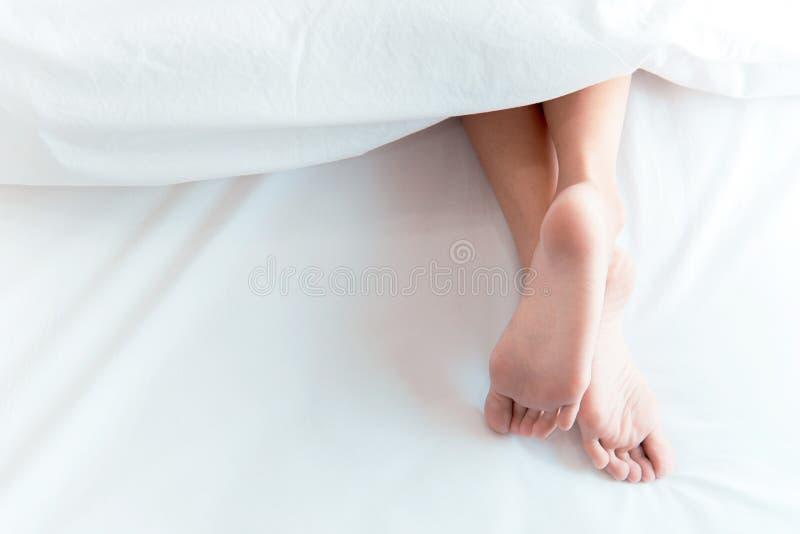 Vrouwenvoeten op het bed onder witte deken Slapend en ontspan concept Vakantie en Vakantiethema stock afbeelding