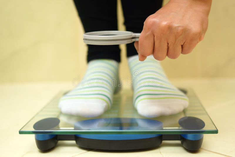 Vrouwenvoeten op weegschaal die gewicht over het overdrijven kijken stock foto's