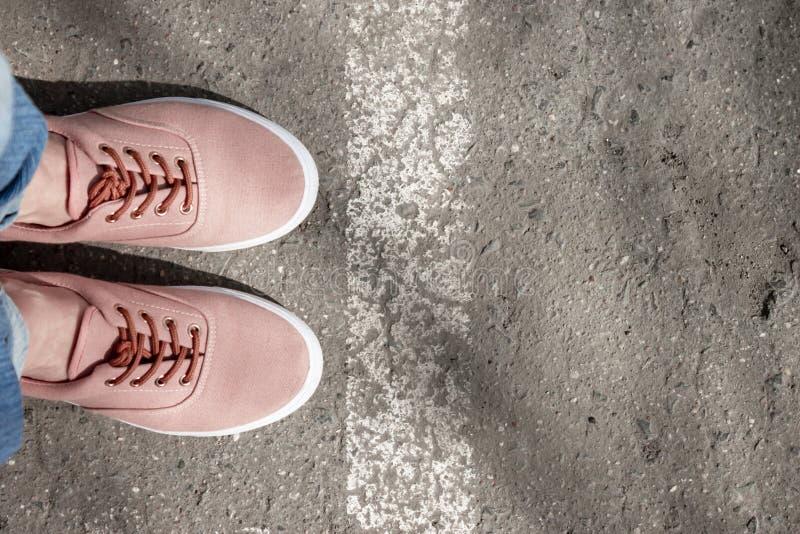 Vrouwenvoeten in oranje tennisschoenen die zich op asfaltweg dichtbij het witte weg merken bevinden royalty-vrije stock afbeeldingen
