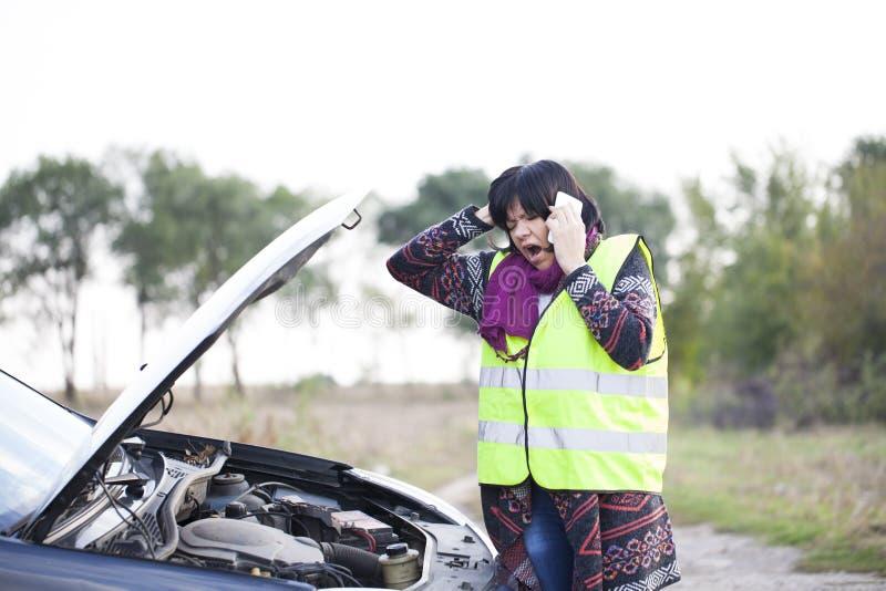 Vrouwenvraag naar hulp wegens een defect de auto op de weg royalty-vrije stock foto