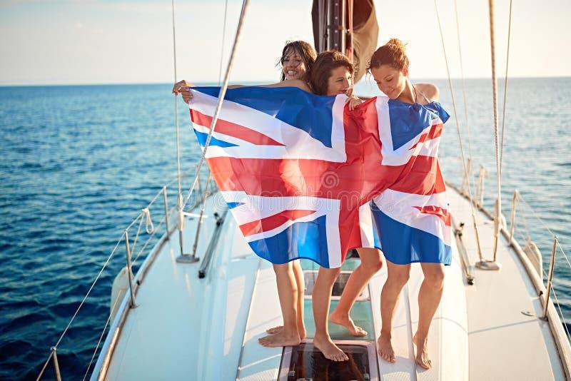 Vrouwenvrienden die op jacht varen en partij hebben bij vakantie stock afbeelding
