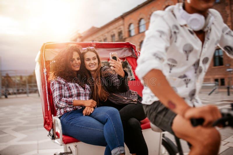 Vrouwenvrienden die selfie op rit met drie wielen nemen royalty-vrije stock afbeeldingen