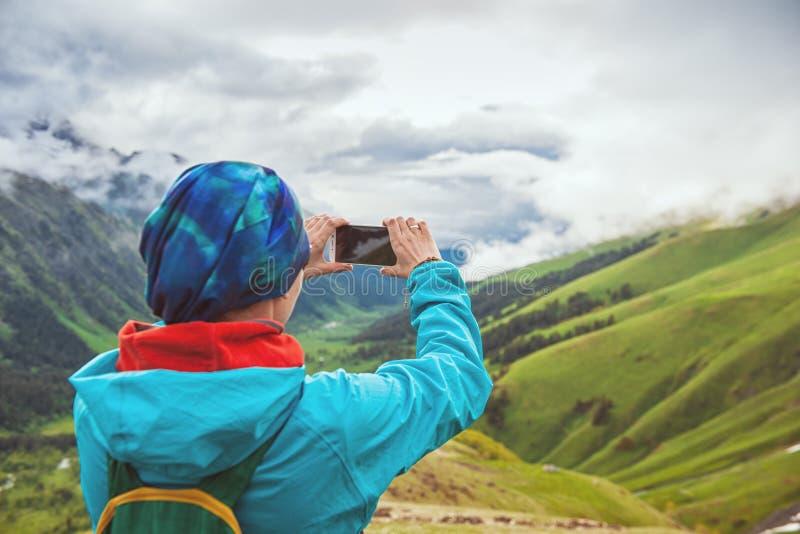 Vrouwenwandelaar die foto op de bovenkant van berg nemen stock foto's