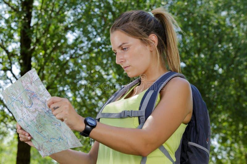 Vrouwenwandelaar die kaart in nationaal park bekijken royalty-vrije stock afbeeldingen