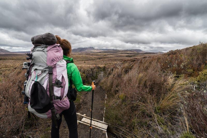Vrouwenwandelaar die met rugzak op het nationale park van Tongariro stappen royalty-vrije stock afbeelding