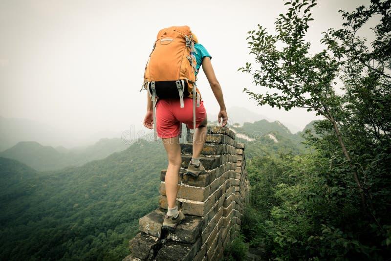 Vrouwenwandelaar die omhoog op de bovenkant van grote muur beklimmen stock afbeeldingen