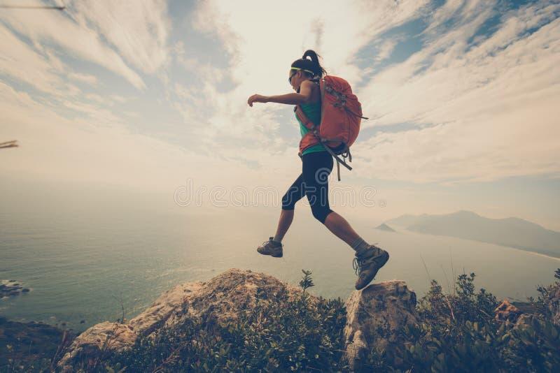 Vrouwenwandelaar die op bergpiek wandelen stock foto's
