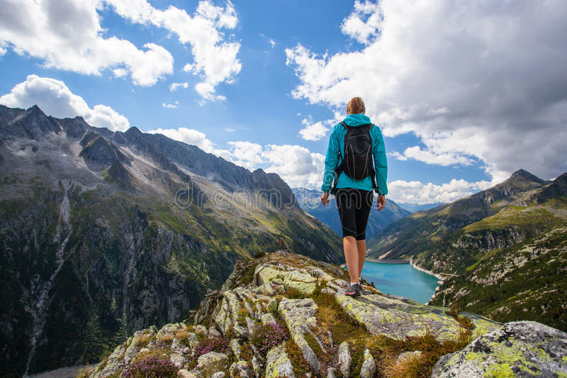 Vrouwenwandelaar op een bovenkant van een berg stock afbeeldingen