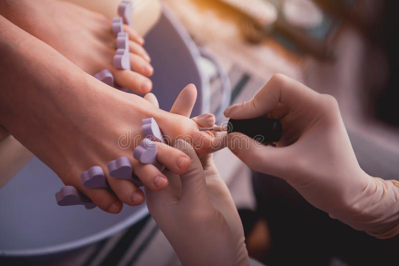 Vrouwenwapen die nagellak toepassen voor cliënt stock foto's