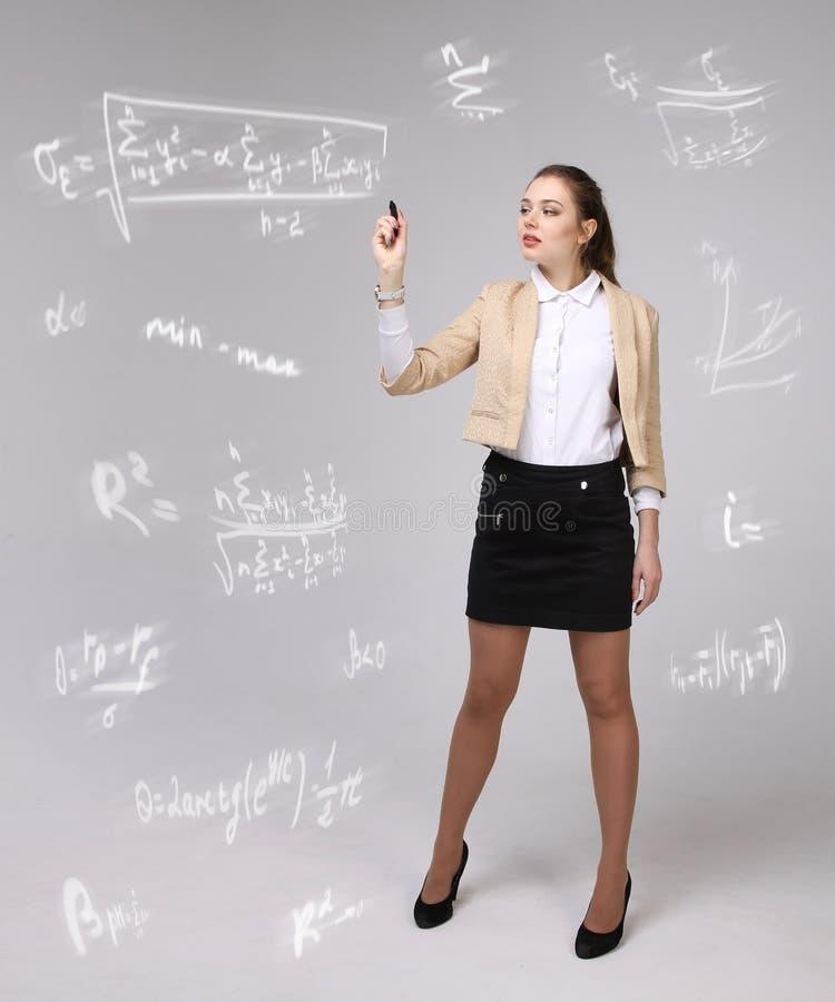 Vrouwenwetenschapper of student die met diverse van de middelbare schoolwiskunde en wetenschap formule werken stock afbeelding