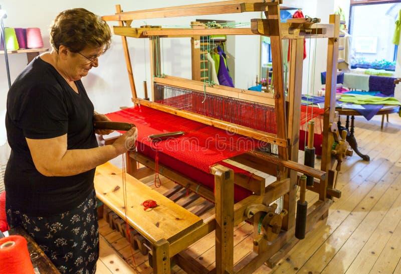 Vrouwenwever die bij het weefgetouw en weefsels het rode tapijt werken royalty-vrije stock afbeeldingen