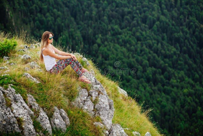 Vrouwenzitting aan het eind van aarde in fascinerend landschap stock afbeeldingen