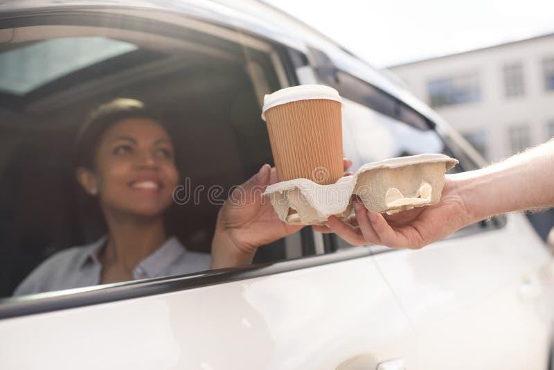 Vrouwenzitting in auto en het kopen koffie om te gaan royalty-vrije stock foto